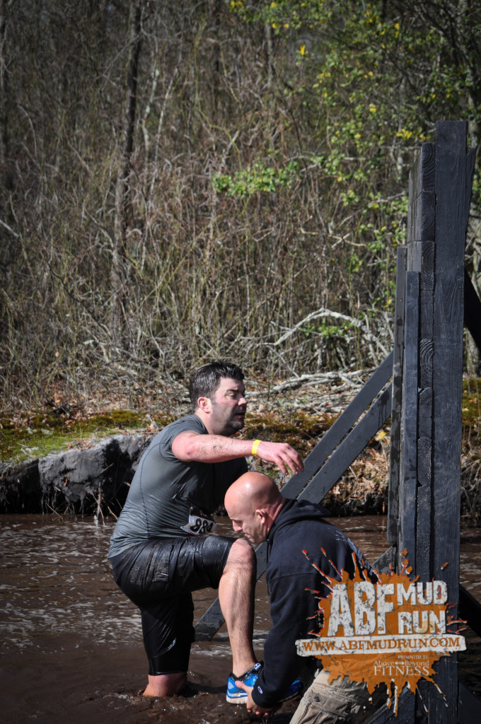 Race Director Chad Mason getting in the mud to help a participant over a wall